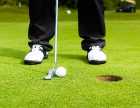 bigstock-Golf-player-putting-ball-into--45071347